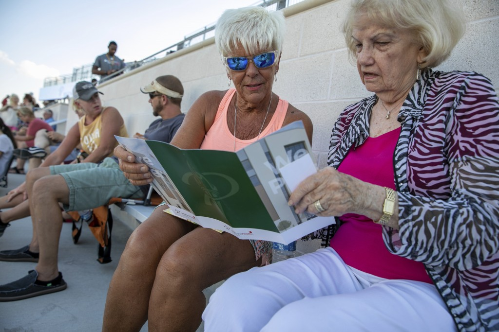 Linda Guthrie, left, and Betty Hughes look at the program during the opening of the new Children's Health Stadium at Prosper ISD on Saturday, Aug. 17,
