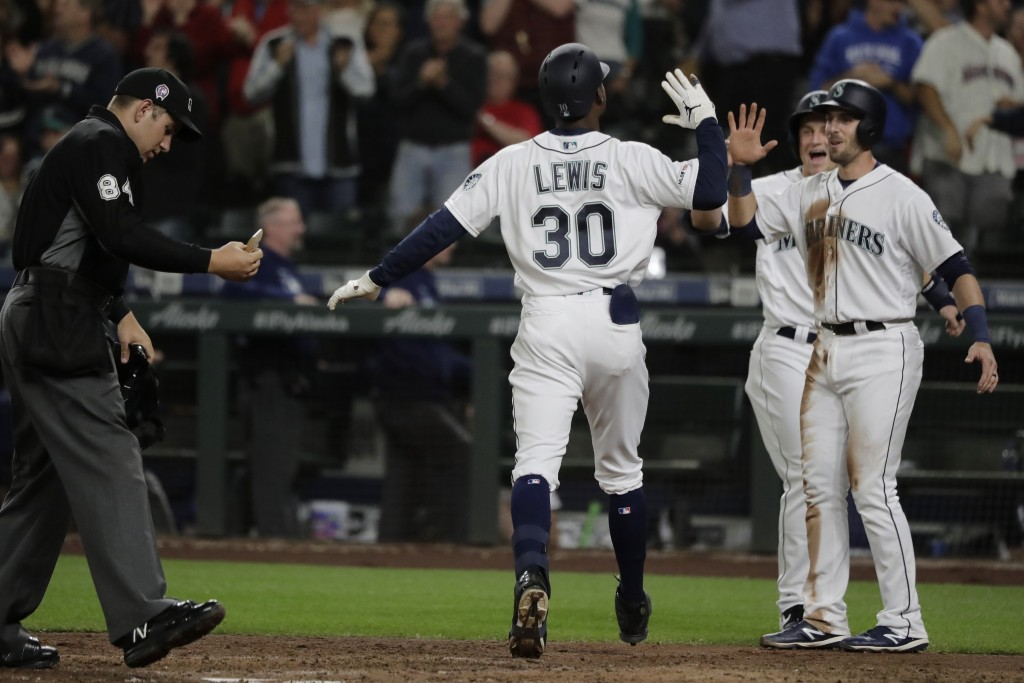 Seattle Mariners' Kyle Lewis (30) greets Austin Nola, right, and Kyle Seager after Seager and Nola scored on a three-run home run by Lewis during the