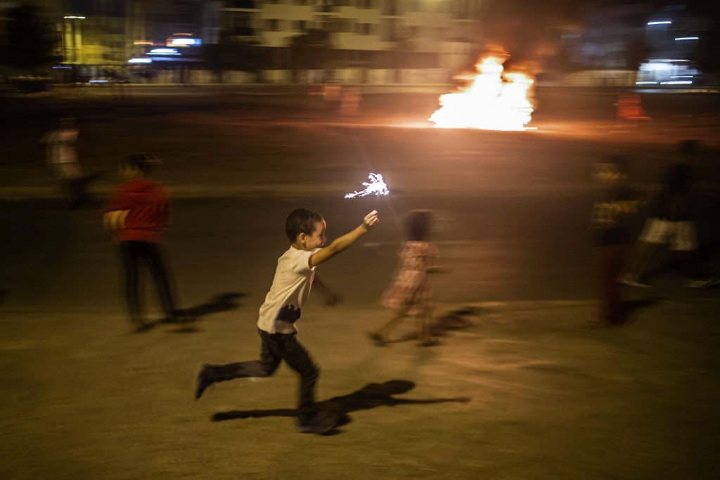 In this Monday, Sept. 9, 2019 photo, a child runs with a sparkler as a bonfire is lit in the distance in celebration of Ashura, in Sale, near Rabat, M...