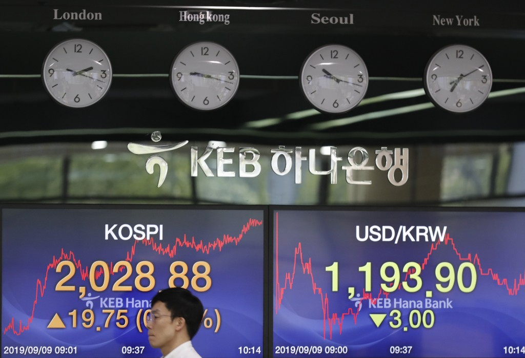 A currency trader walks by the screens showing the Korea Composite Stock Price Index (KOSPI), left, and the foreign exchange rate between U.S. dollar