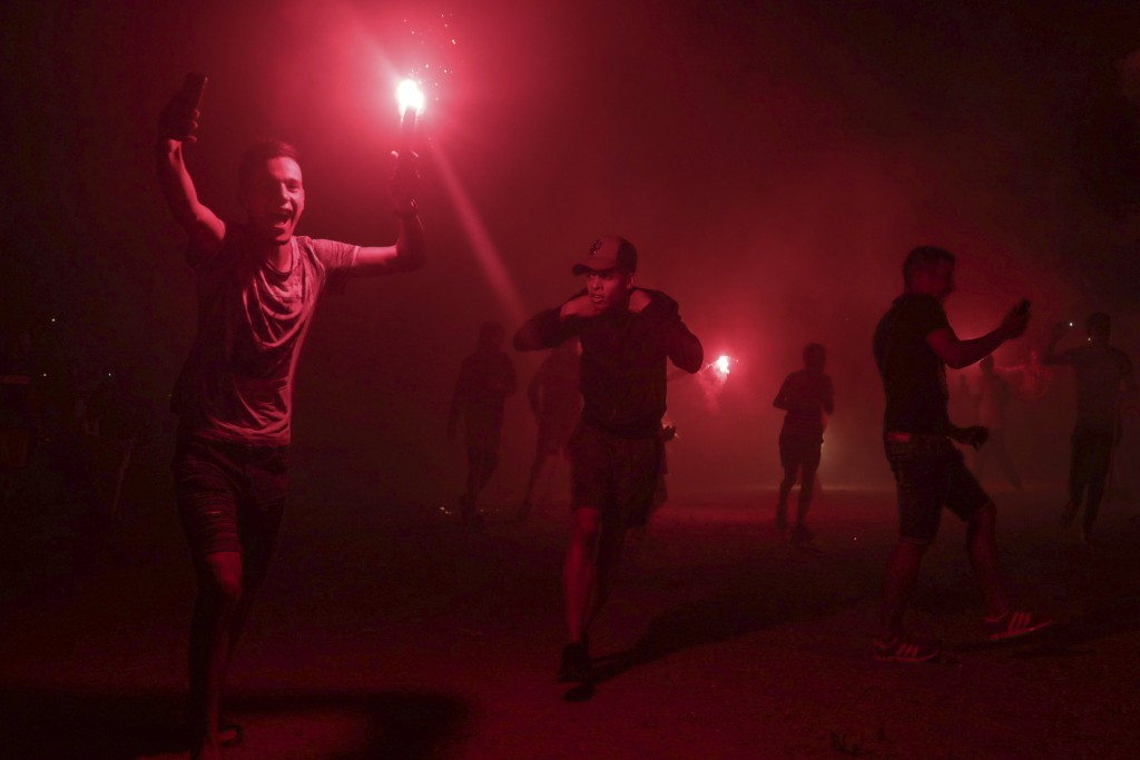 In this Monday, Sept. 9, 2019 photo, youths, mostly football ultras, light flares in celebration of Ashura, in Sale, near Rabat, Morocco. On Sept. 9, ...