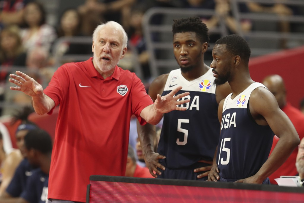 United States' coach Gregg Popovich, left talks to United States' Donovan Mitchell, center and United States' Kemba Walker at right for the FIBA Baske...