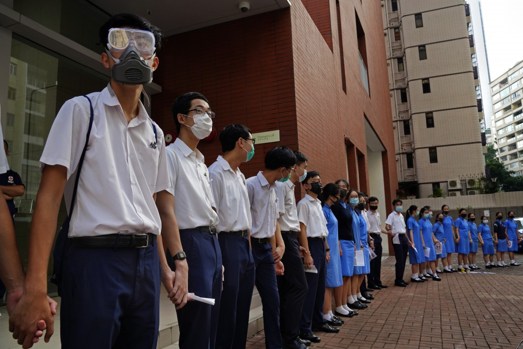 Students form human chain outside St. Paul's Co-Educational College in Hong Kong, Monday, Sept. 9, 2019. Students and alumni of the school protest to