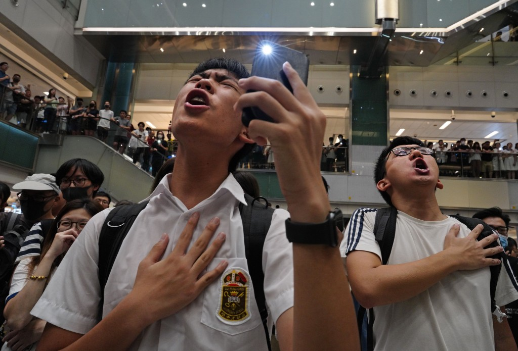 "Local residents sing a theme song written by protesters ""Glory be to thee"" at a shopping mall in Hong Kong Wednesday, Sept. 11, 2019. Hong Kong Chief"
