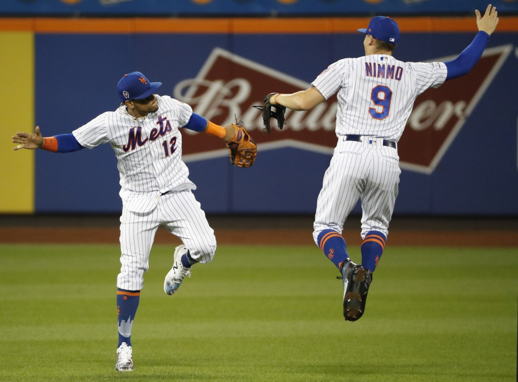 New York Mets center fielder Juan Lagares, left, leaps to celebrate with right fielder Brandon Nimmo (9) after the Mets' 9-0 win over the Arizona Diam...