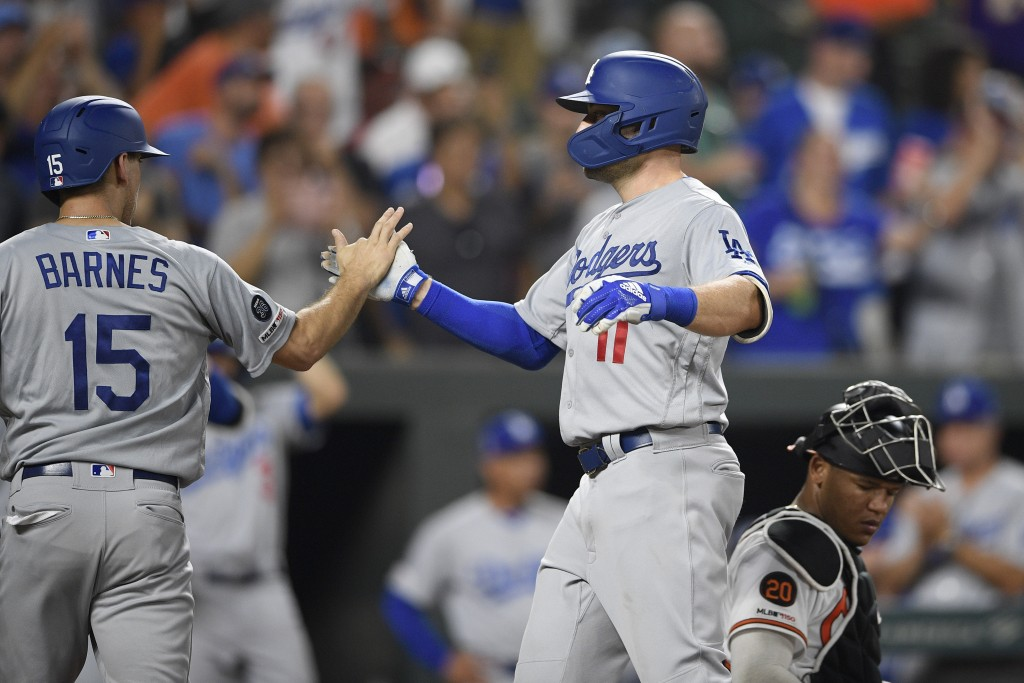 Los Angeles Dodgers' A.J. Pollock celebrates his two-run with Austin Barnes (15) during the sixth inning of a baseball game as Baltimore Orioles catch...