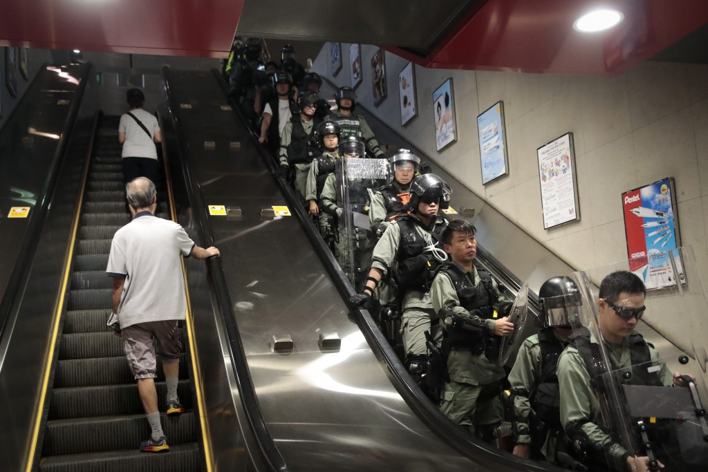 In this Monday, Sept. 2, 2019, photo, two commuters ride an escalator at a train station past police officers in riot gear deployed to arrest proteste...