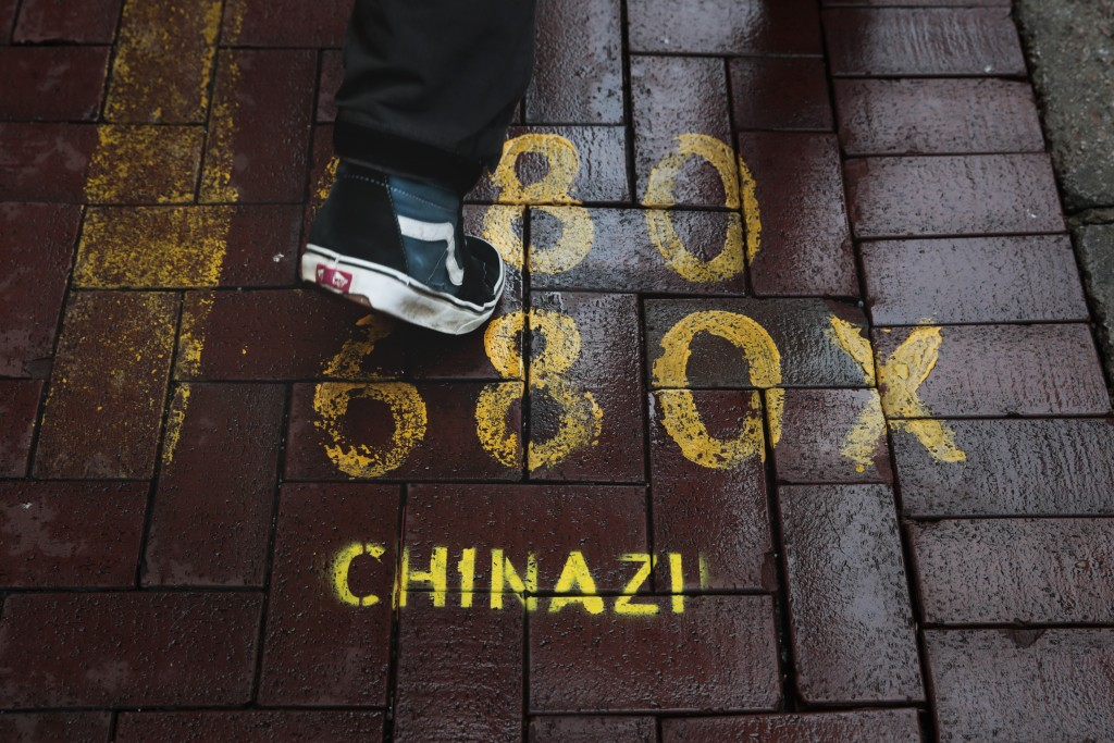 "In this Sept. 4, 2019, photo, a man walks past a bus stop spray-painted with an anti-China slogan ""Chinazi"" in Hong Kong. Life is not quite normal aft..."