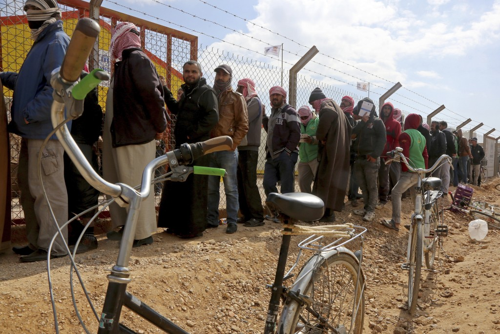 FILE - In this Feb. 18, 2018 file photo, Syrian refugees line up to register their names at an employment office, at the Azraq Refugee Camp, 100 kilom