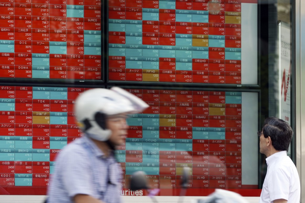 A man looks at an electronic stock board showing Japan's Nikkei 225 index at a securities firm in Tokyo Thursday, Sept. 12, 2019. Asian shares were mi...