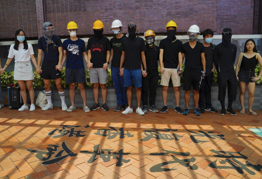 Students from Hong Kong University join their hands and shout slogans near Chinese calligraphy on the floor outside their school in Hong Kong, Monday,