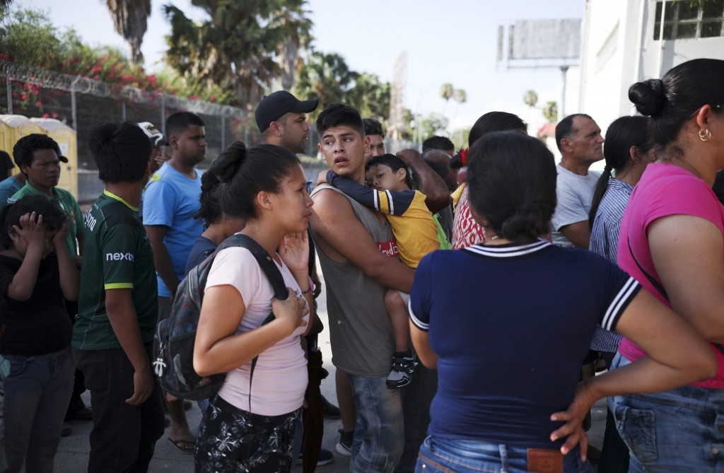 FILE - In this Aug. 1, 2019 file photo, migrants line up in Matamoros, Mexico, for a meal donated by volunteers from the U.S., at the foot of the Puer...