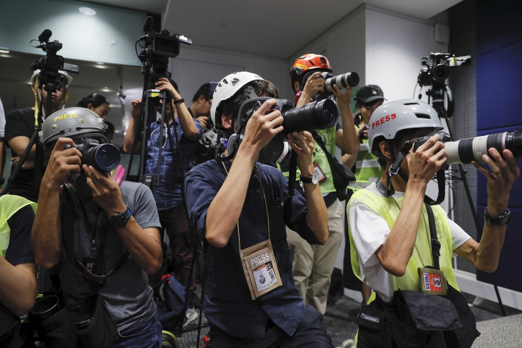 In a sign of protest against the police using force against the media, press photographers wear protective gear during a police media conference in Ho