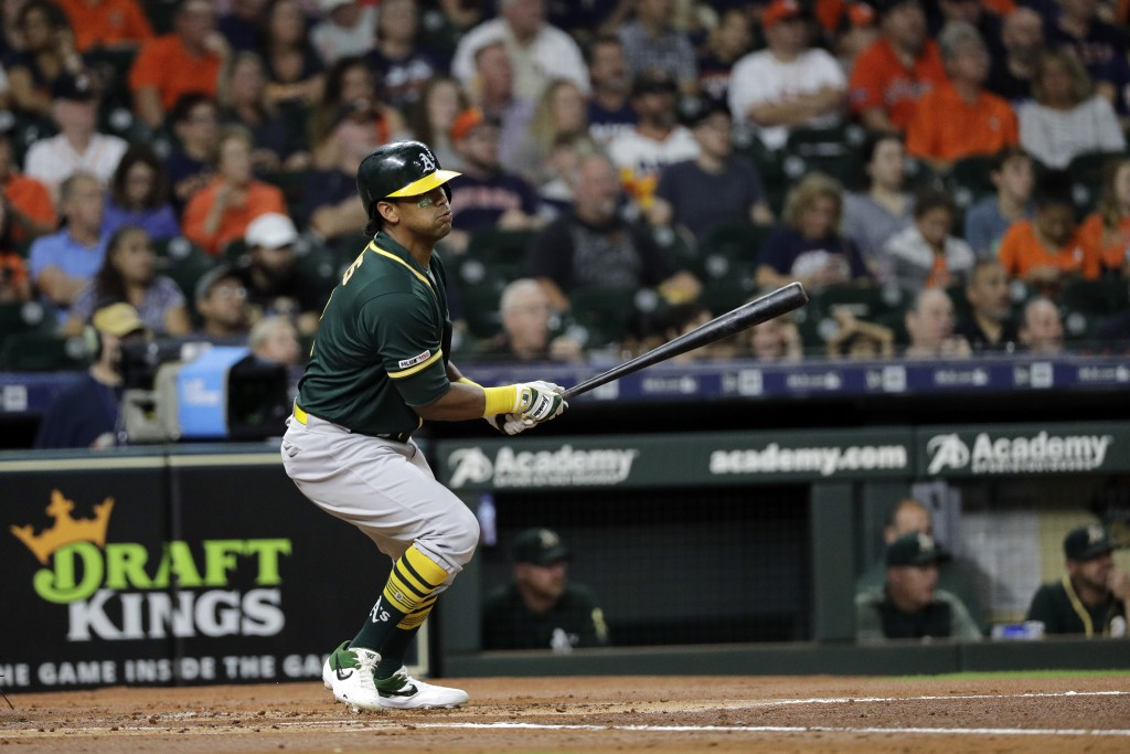 Oakland Athletics' Khris Davis hits an RBI single against the Houston Astros during the first inning of a baseball game Tuesday, Sept. 10, 2019, in Ho...
