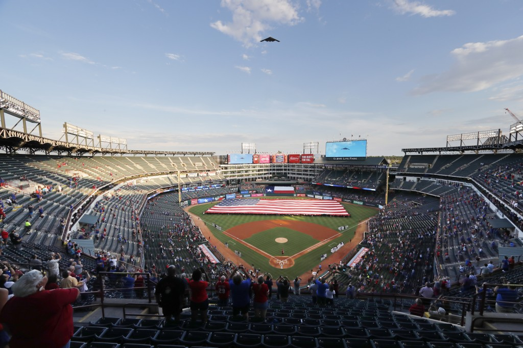 A B-2 bomber flies over Globe Life Park during the playing of the national anthem before a baseball game between the Tampa Rays and Texas Rangers in A...