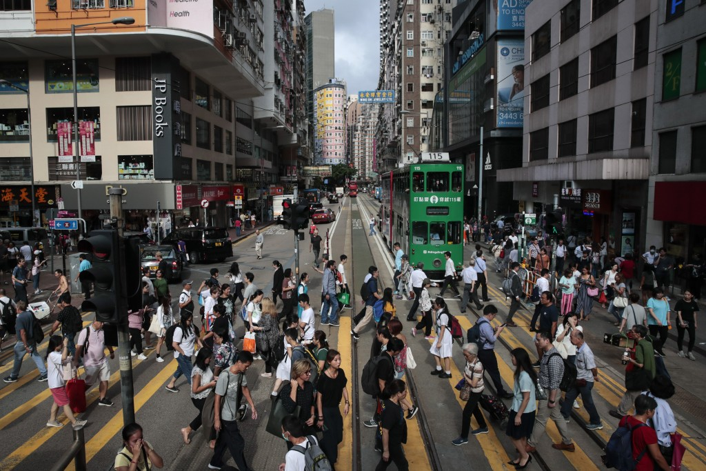 In this Sept. 3, 2019, photo, pedestrians cross a street in the Wan Chai district of Hong Kong. Life is not quite normal after three months of steady ...
