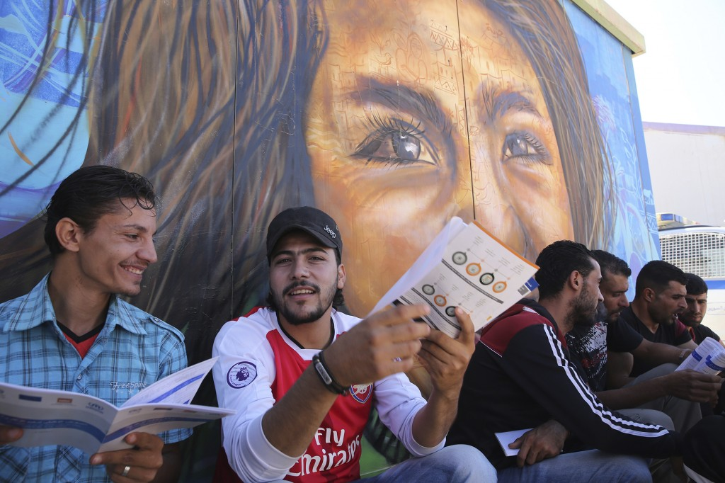 FILE - In this Oct. 4, 2017 file photo, Syrian refugees read brochures during a EU-sponsored job fair in Zaatari, Jordan's largest camp for Syrian ref