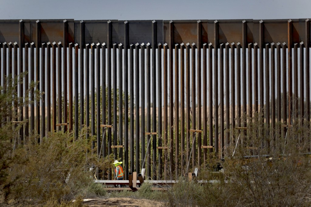 A government contractor walks beside a completed section of Pentagon-funded border wall along the Colorado River, Tuesday, Sept. 10, 2019 in Yuma, Ari