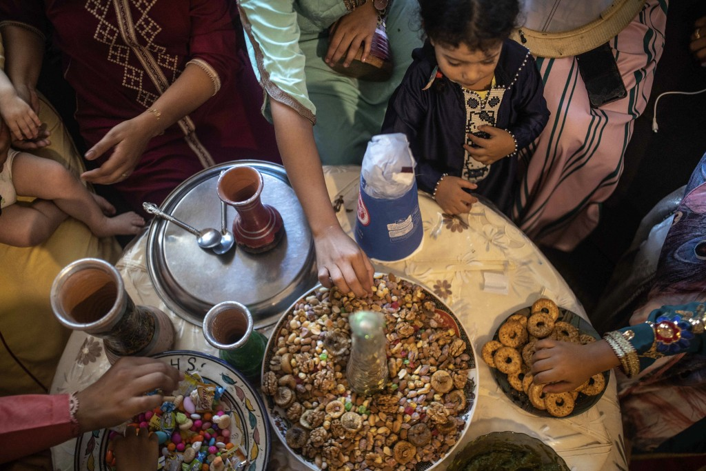 In this Tuesday, Sept. 10, 2019 photo, woman and children eat dried fruits and treats at a home to celebrate the occasion of Ashura, in Sale, near Rab...