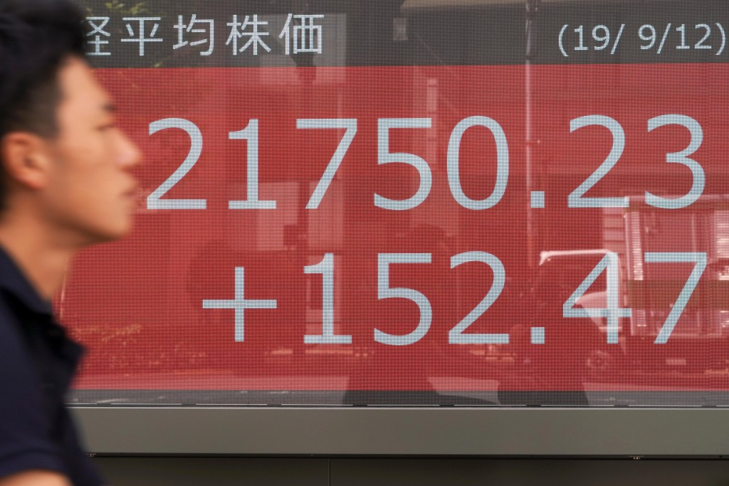 A man walks past an electronic stock board showing Japan's Nikkei 225 index at a securities firm in Tokyo Thursday, Sept. 12, 2019. Asian shares were ...
