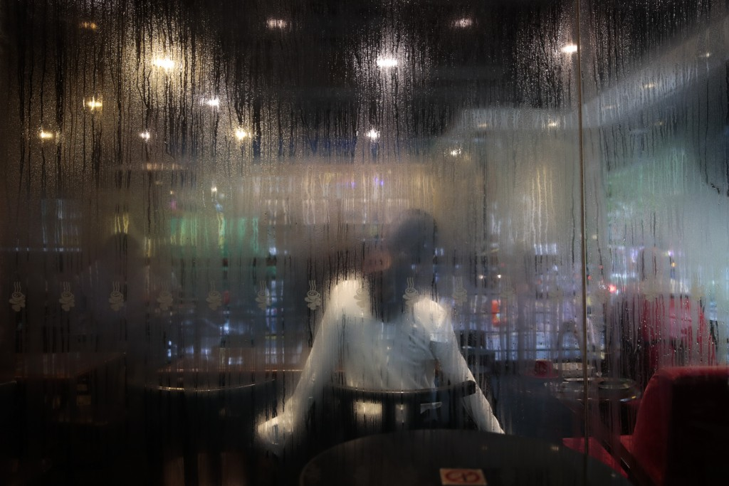 In this Sept. 2, 2019, photo, a woman stretching at a coffee shop is seen through a window with condensation in Hong Kong. Life is not quite normal af...