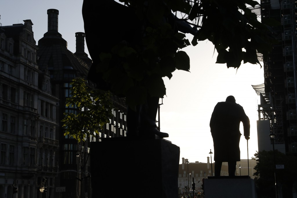 The statue of former British Prime Minister Winston Churchill is silhouetted against the sky early morning in London, Thursday, Sept. 12, 2019. (AP Ph...