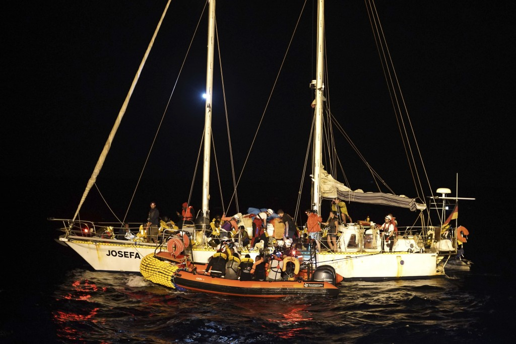 Migrants are transferred onto a dinghy from a 14-meter sailboat Josefa, run by the group Resqship, after being rescued near the Bouri Oil Fields, to b