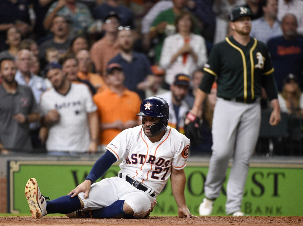Houston Astros' Jose Altuve, left, reacts after being tagged out at home, as Oakland Athletics starting pitcher Brett Anderson, back right, walks back