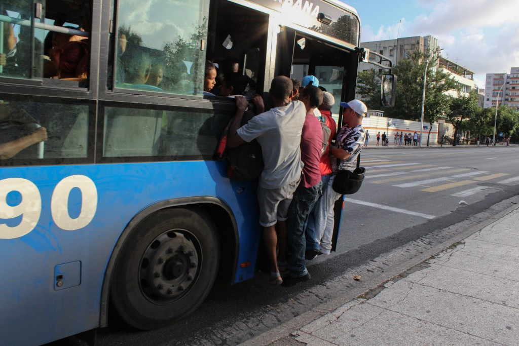 Locals hang precariously from a public service bus in Havana, Cuba, Wednesday, Sept. 11, 2019. The island nations is facing a diesel fuel shortage, bu