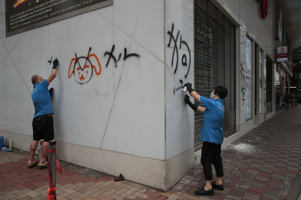 In this Sept. 1, 2019, photo, workers remove graffiti left by protesters during a protest the night before in Hong Kong. Life is not quite normal afte...