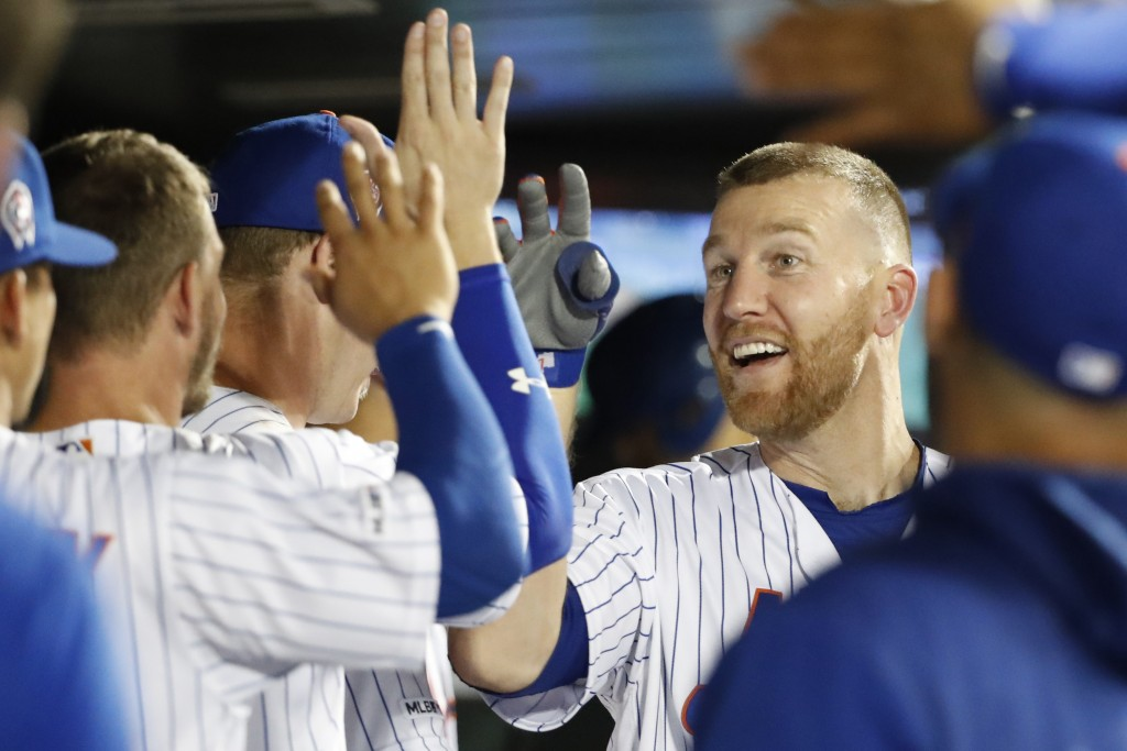 New York Mets' Todd Frazier celebrates with teammates in the dugout after hitting a solo home run, his second homer run of the night, during the third...
