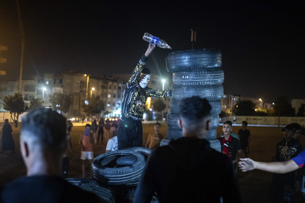 In this Monday, Sept. 9, 2019 photo, a youth pours kerosene over tires to light a bonfire in celebration of Ashura, in Sale, near Rabat, Morocco. On S