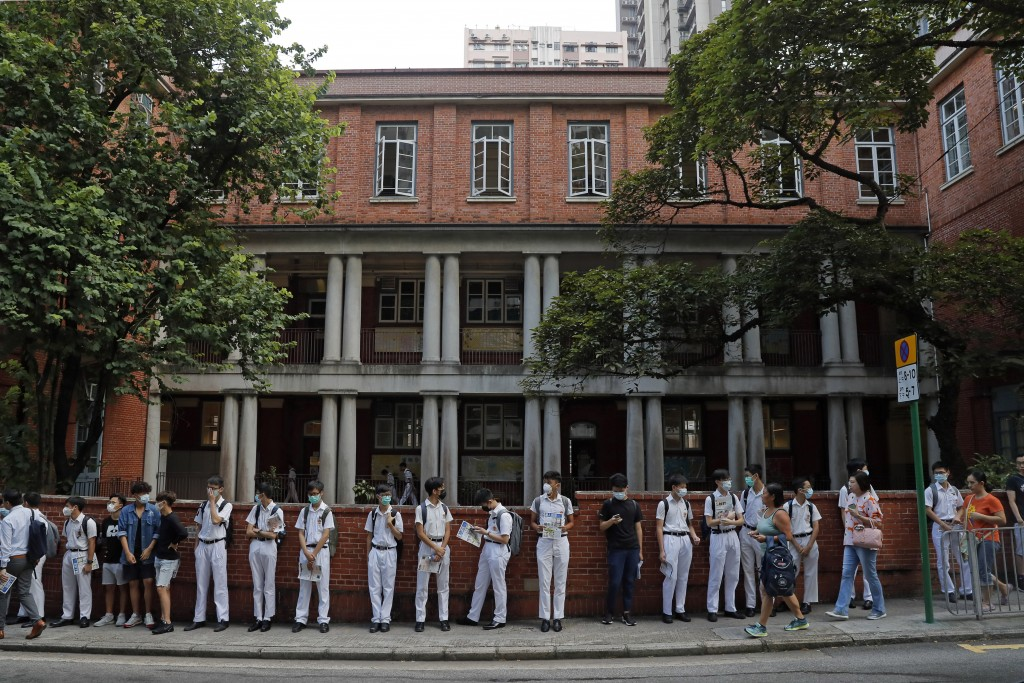 Students wearing mask stand around King's College in Hong Kong, Monday, Sept. 9, 2019. Thousands of demonstrators in Hong Kong urged President Donald ...