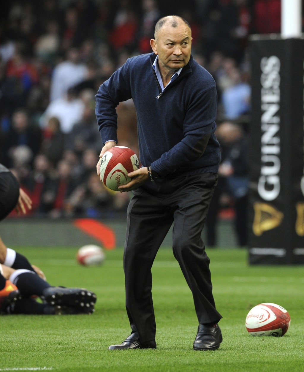 FILE - In this Feb. 23, 2019, file photo, England rugby head coach Eddie Jones prepares to pass the ball as his team prepares for the Six Nations rugb...