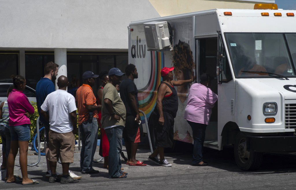 People line up to buy pre-paid cell phone cards, for sale from a mobile Aliv office, after the passing of Hurricane Dorian in Freeport, Bahamas, Wedne...