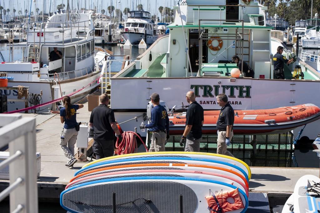 Authorities walk outside the Truth, a Truth Aquatics-owned dive boat, docked in the Santa Barbara Harbor in Santa Barbara, Calif., Sunday, Sept. 8, 20...