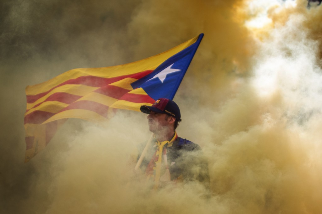 A man holding an independence flag is seen through the smoke thrown by demonstrators during the Catalan National Day in Barcelona, Spain, Wednesday, S...