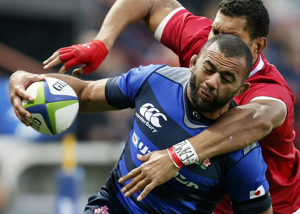FILE - In this Saturday, Nov. 18, 2017 file photo, Japan's Michael Leitch is tackled by Tonga's Steve Mafi during a rugby union international match at
