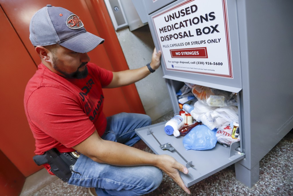 In this Sept. 11, 2019, photo, narcotics detective Paul Laurella retrieves unused medications from the police department's disposal box in Barberton,