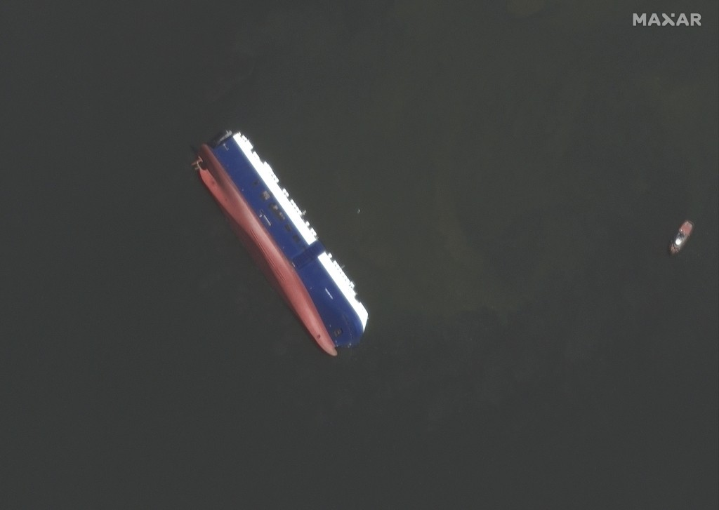 This Sept. 10, 2019 satellite photo provided by Maxar Technologies, shows the capsized cargo shop Golden Ray in Jekyll Island, Ga. A fire broke out ab
