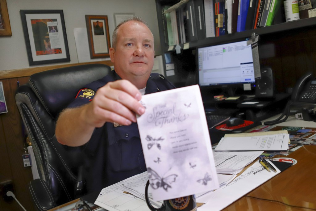 In this Sept. 11, 2019, photo, Barberton Police Chief Vincent Morber shows a copy of a thank-you card that was sent to the department in Barberton, Oh...