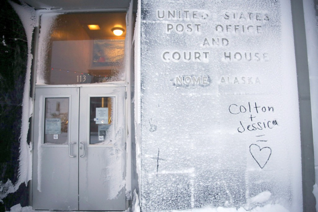 In this Feb. 13, 2019, photo, the names of two lovers are etched onto a snow-covered wall of the United States Post Office and Court House in Nome, Al...
