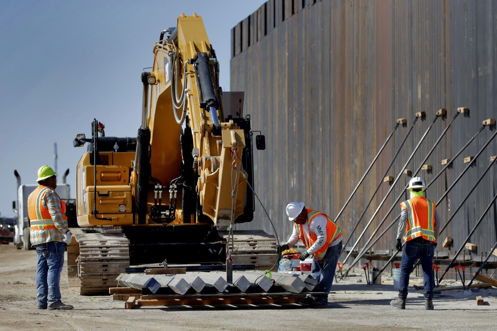Government contractors erect a section of Pentagon-funded border wall along the Colorado River, Tuesday, Sept. 10, 2019 in Yuma, Ariz. The 30-foot hig...