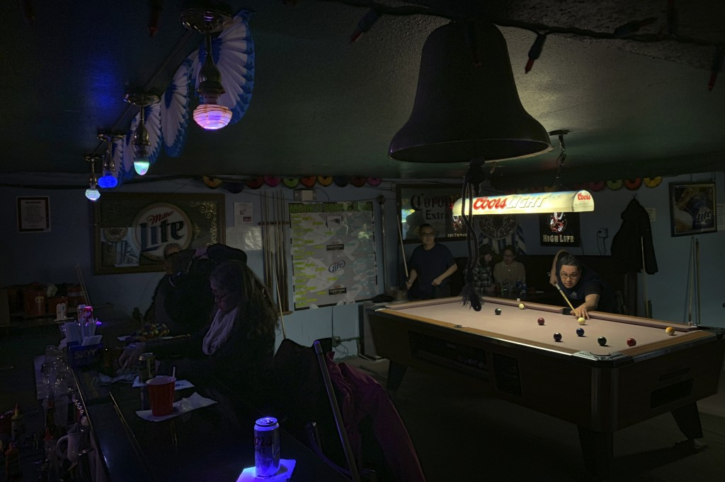 In this Feb. 23, 2019, photo, people play pool while some sit at the bar with their drinks at Soap and Suds, a popular nighttime spot, on Front Street...