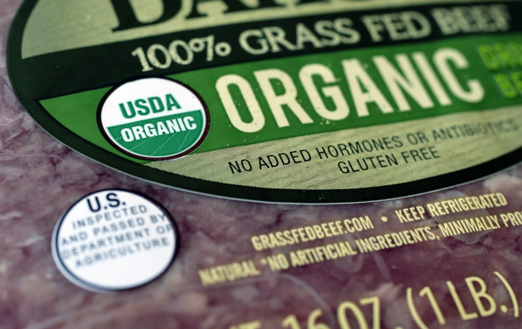 """FILE - In this July 9, 2018 photo a """"USDA Organic"""" label is printed on the label of a pound of ground beef, in Walpole, Mass. Labels such as """"Fair Tra..."""