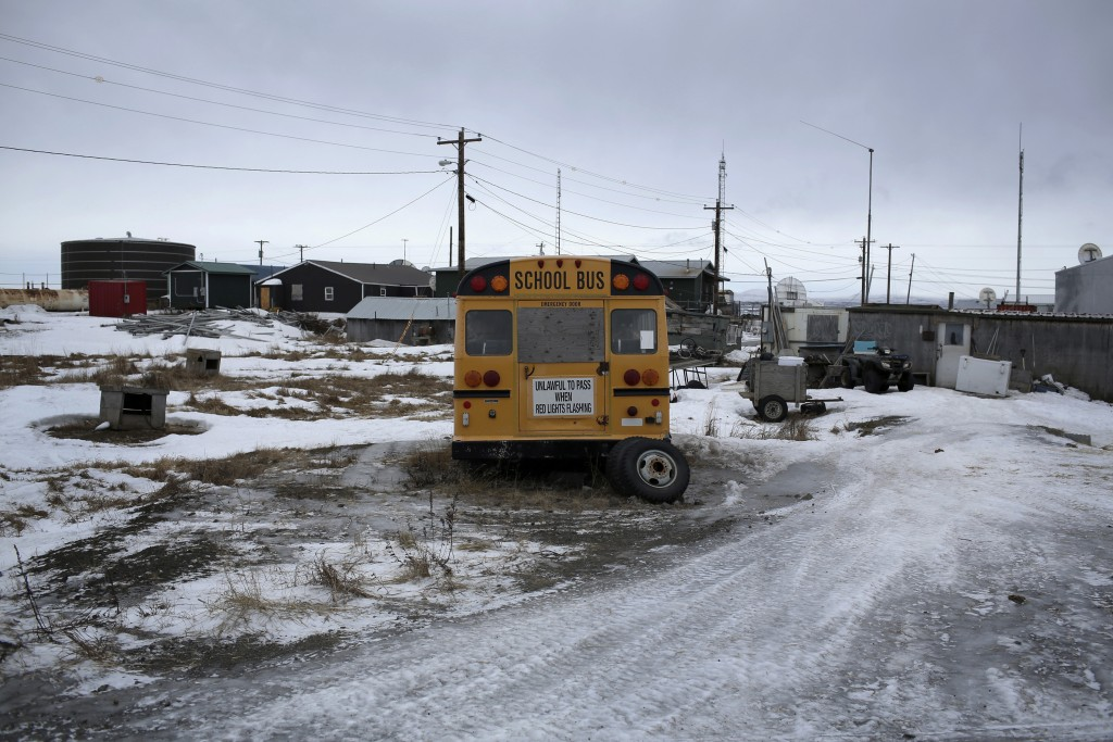 In this Feb. 18, 2019, photo, a yellow school bus is parked outside a residential area in the Native Village of St. Michael, Alaska. According to a li...