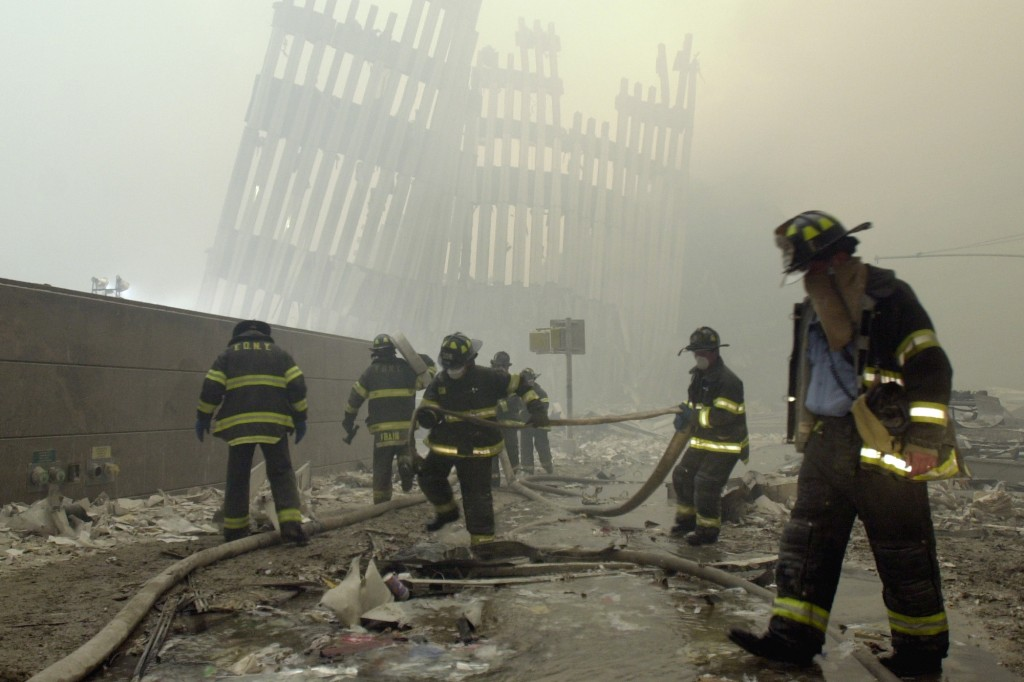 FILE - In this Sept. 11, 2001, file photo, firefighters work beneath the destroyed mullions, the vertical struts that once faced the outer walls of th