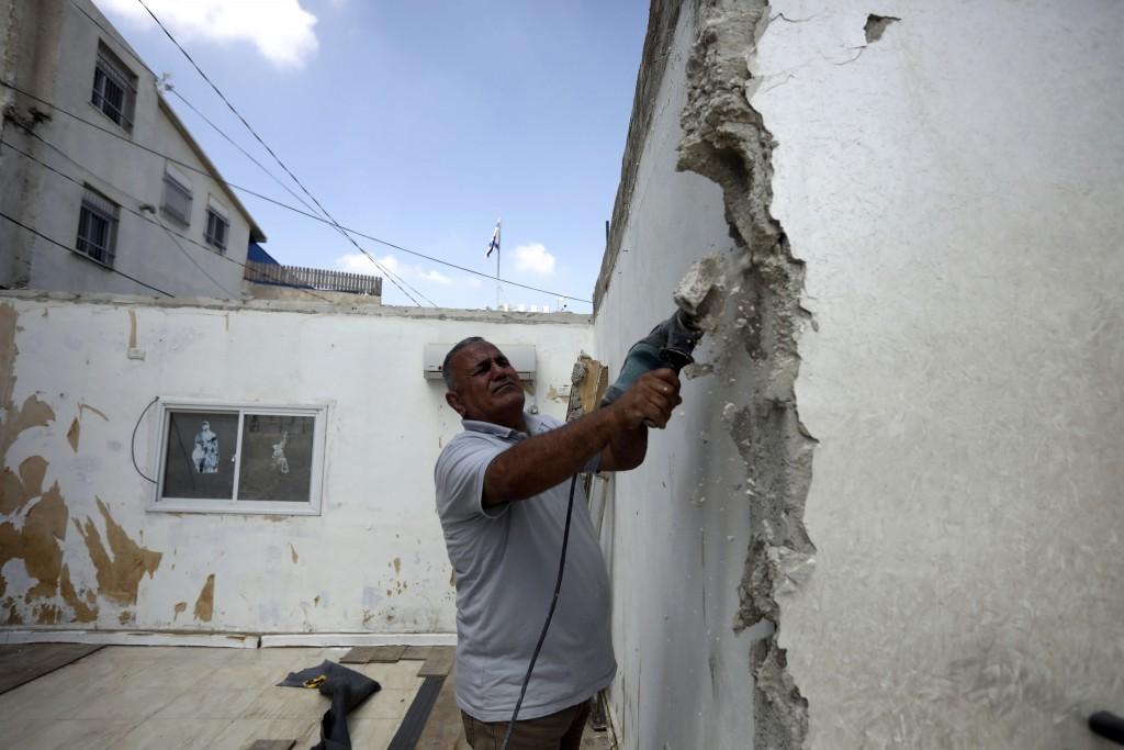 In this Monday, Sept. 9, 2019 photo, Palestinian Jamil Masalmeh uses a power tool to destroy an apartment he had added to his home years earlier, in t
