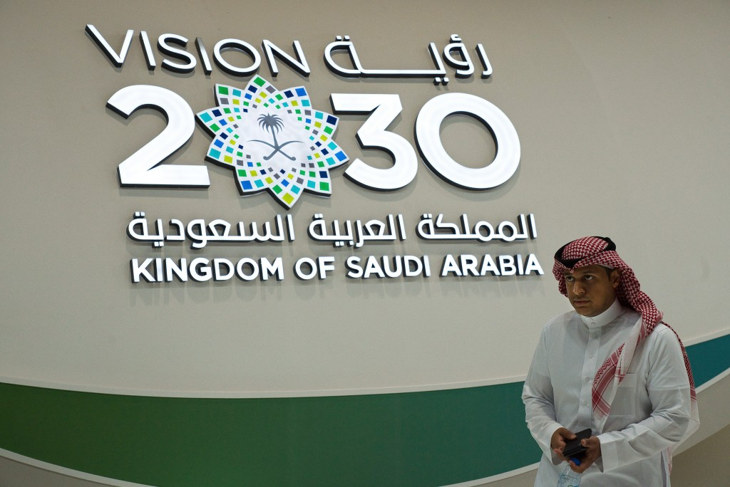 """A Saudi man walks past a """"Vision 2030"""" display at a stand about Saudi Arabia during the World Energy Congress in Abu Dhabi, United Arab Emirates, Tues"""