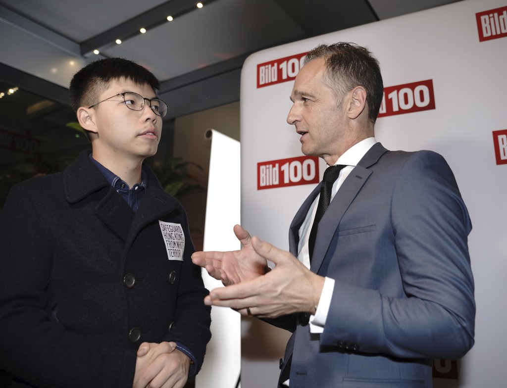 German Foreign Minister Heiko Maas, right, talks to Hong Kong activist Joshua Wong, left, during a reception of a German news paper in Berlin, Germany